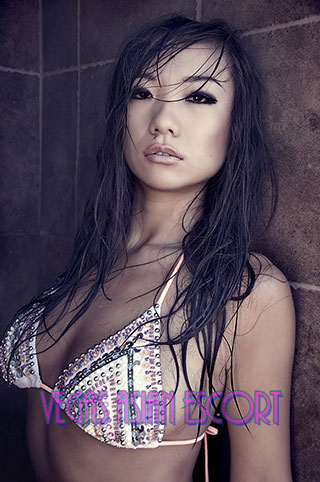 Asian escort Las Vegas with wet hair poses against wall to show off her exotic look.